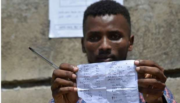 Tigistu Tesfaye, a Hawassa city resident and election observer, checking vote results at one of the