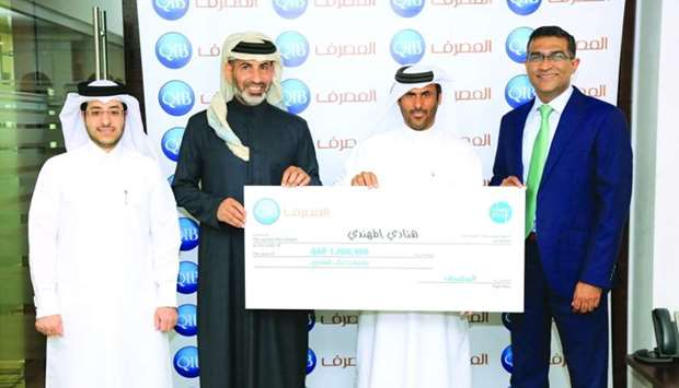 Hanady Mohamed al-Mohannadi's husband receiving the QR1mn cheque on her behalf.