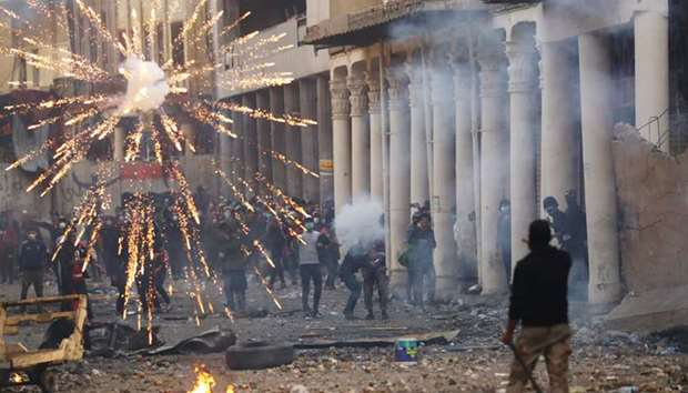 Iraqi demonstrators throw fireworks towards Iraqi security forces during the ongoing anti-government