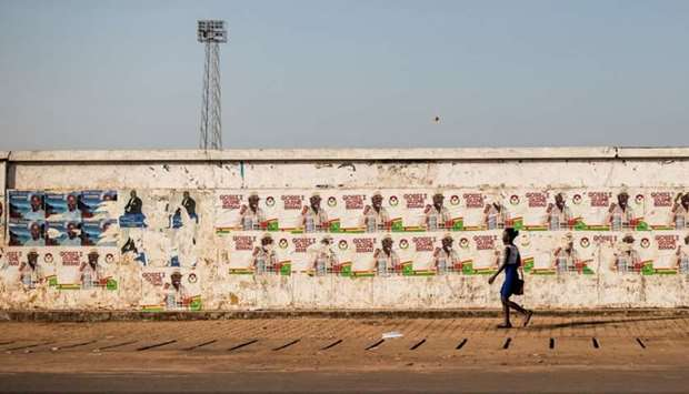 A woman walks past election campaign posters on the eve of the presidential elections in Guinea-Biss