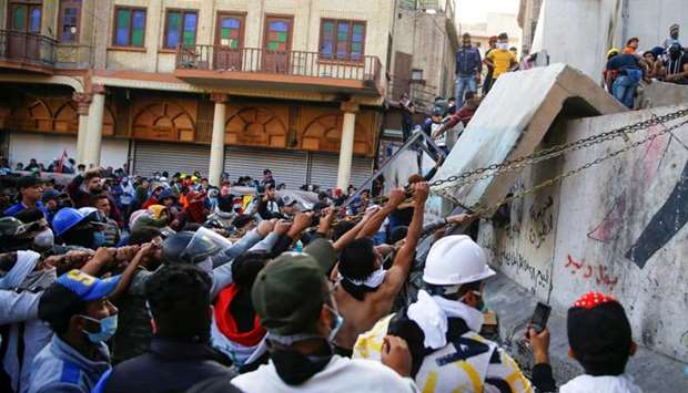 Iraqi demonstrators try to pull down concrete walls during the ongoing anti-government protests in B