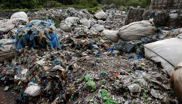 Scrap from an illegal plastic recycling factory are dumped near a palm oil plantation in Jenjarom, K