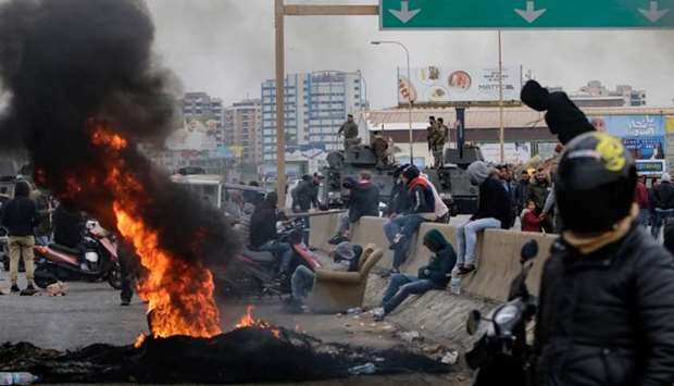 Lebanese anti-government protesters burn tyres to block the road leading to the southern entrance of