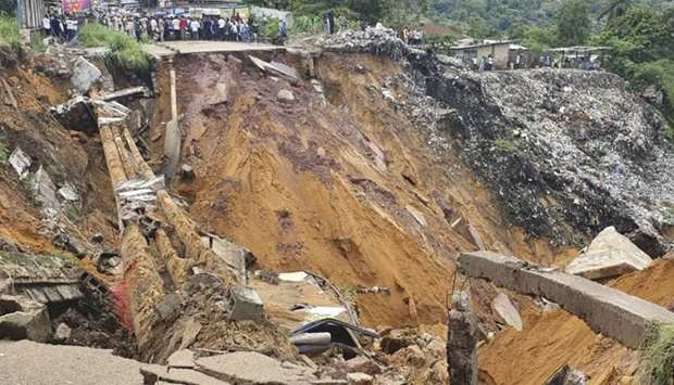 A road surface swept away by a landslide caused by torrential overnight rains is photographed in the