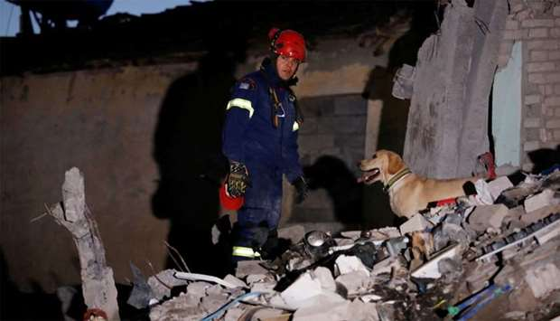 A member of the emergency personnel from Greece works at a damaged building, following Tuesday's pow