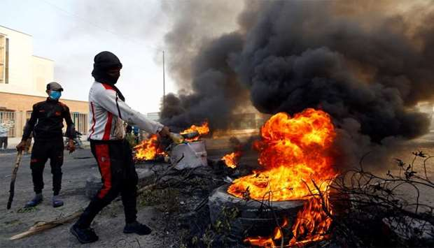 Protester pours fuel on a tire to burn it as he blocks a street during ongoing anti-government prote