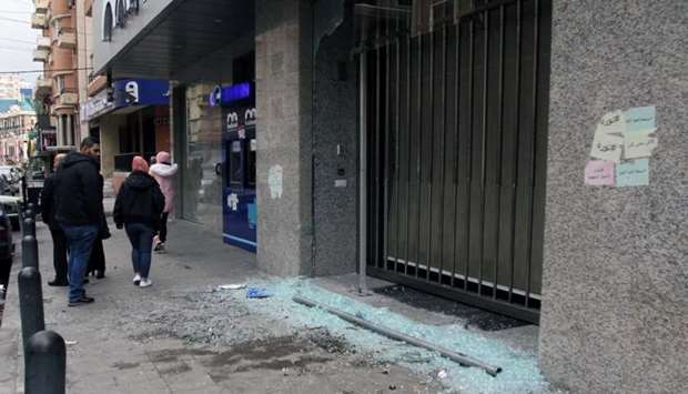 Men walk near broken glass from a damaged Bankmed branch in Tripoli, Lebanon