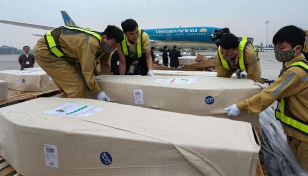 Ground personnel of Noi Bai International Airport preparing caskets containing the remains of Vietna