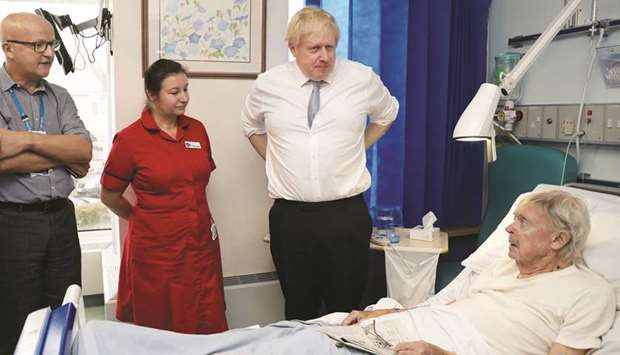 Prime Minister Boris Johnson speaks to patient Andrew Hall as he visits West Cornwall Community hosp