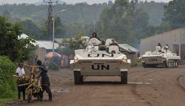 Congolese men push their makeshift bicycle past UN peacekeepers