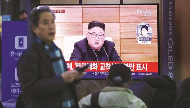 People watch a TV broadcasting file footage for a news report on North Korea firing an unidentified