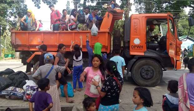 Residents, whose village were affected by a landslide due to a 6.5-magnitude earthquake, disembark f