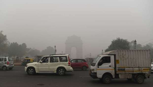 Motorists drive along a road under heavy smog conditions near India Gate