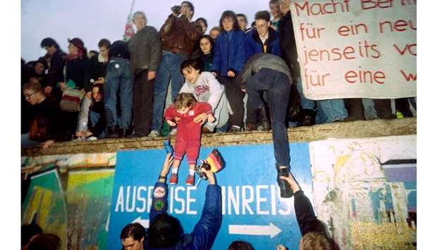 In this file photo taken on December 22, 1989 people from East Germany greet citizens of West German