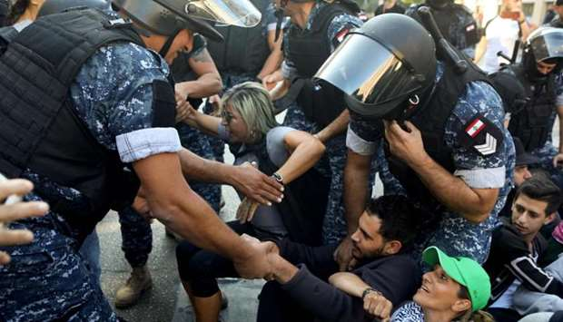 Lebanese security forces try to remove demonstrators blocking a road in a central neighbourhood of t