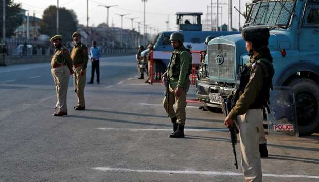 Policemen stand guard on a road in Srinagar on October 31