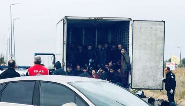 Migrants are seen inside a refrigerated truck found by police, after a check at a motorway near Xant