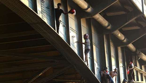 Iraqi demonstrators climb Al Jumhuriya bridge during the ongoing anti-government protests in Baghdad