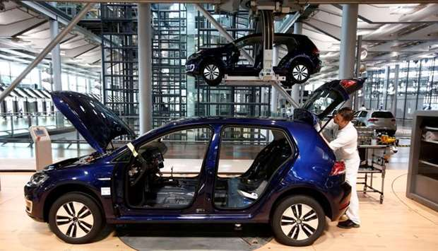 A worker assembles an e-Golf electric car at a production line of German carmaker Volkswagen in Dres