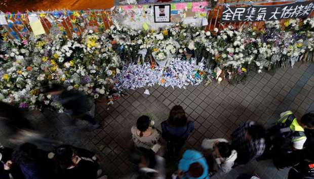 People gather near a makeshift memorial, paying tribute to Chow Tsz-lok, 22, a university student wh