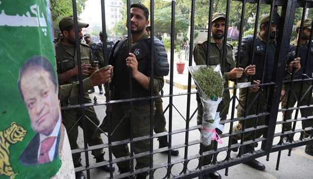 Pakistani policemen stand guard on the gate of a hospital before shifting jailed Pakistan's former p