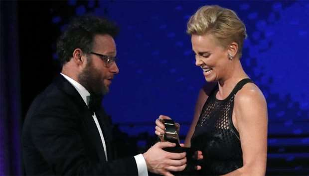 Charlize Theron accepts her award from presenter Seth Rogen.