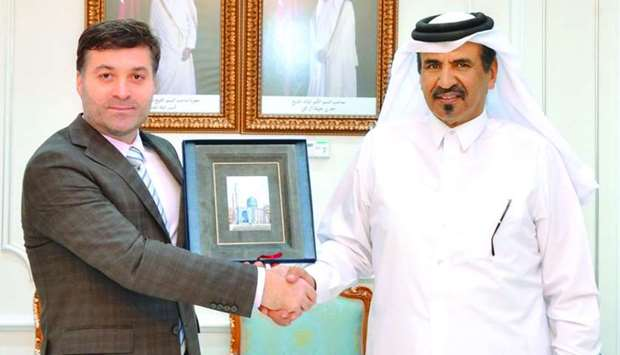 Al-Kuwari and Abubakarov shaking hands during a meeting at the Qatar Chamber's Doha headquarters.