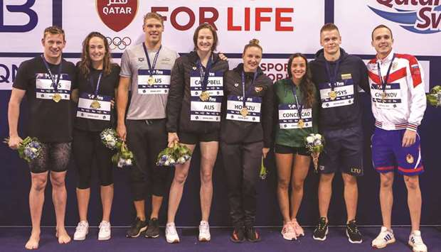 Swimmers pose with their medals on the final day of the FINA Swimming World Cup at the Hamad Aquatic