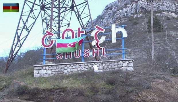 An Azeri flag hanging on a sign reading Shushi in Russian and Armenian (Shusha in Azerbaijani) on th