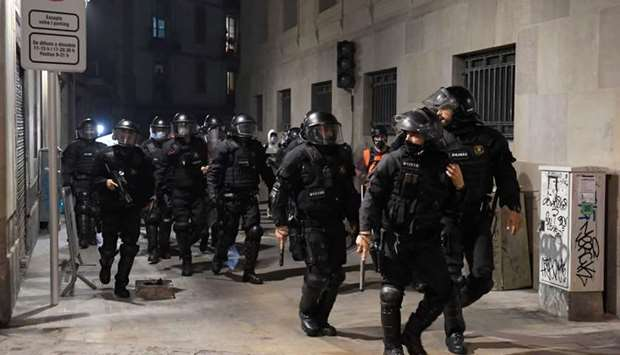 Catalan anti-riot police officers patrol a street during a demonstration against evictions amid the