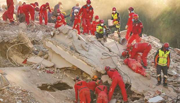 Rescue personnel search for survivors in the debris of a collapsed building in the Bayrakli district