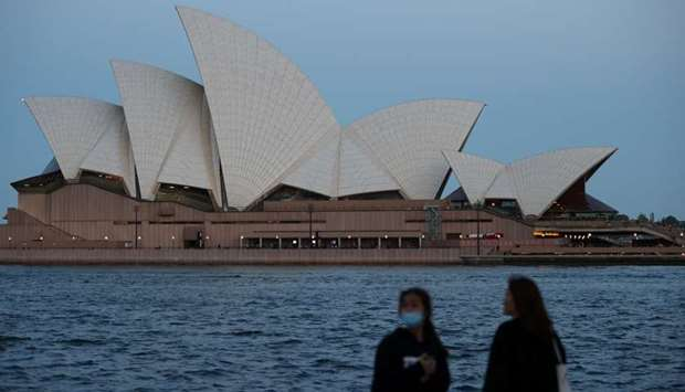 People stand on the harbour waterfront near the Sydney Opera House in Sydney, Australia