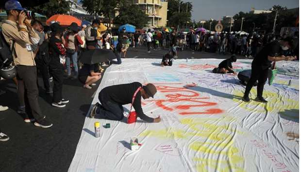 People write on poster during a rally to call for the ouster of Prime Minister Prayuth Chan-ocha's g