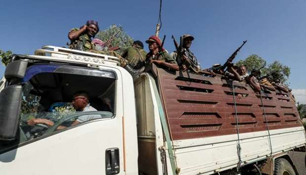 Members of Amhara region militias ride on their truck as they head to face the Tigray People's Liber