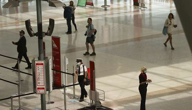 A masked crew member approaches security in a domestic terminal at Sydney Airport in Sydney