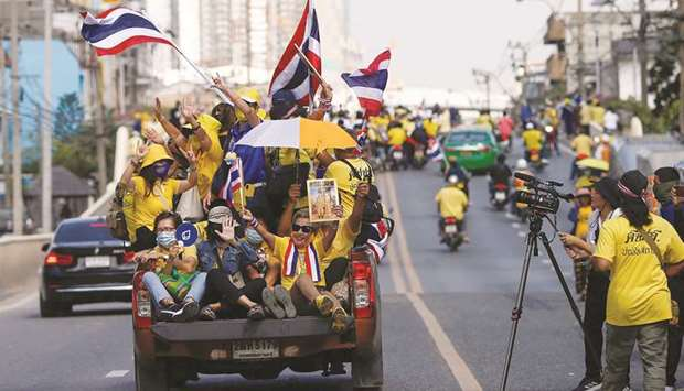 Royalists hold national flags while riding towards a rally in front of the parliament, to show their