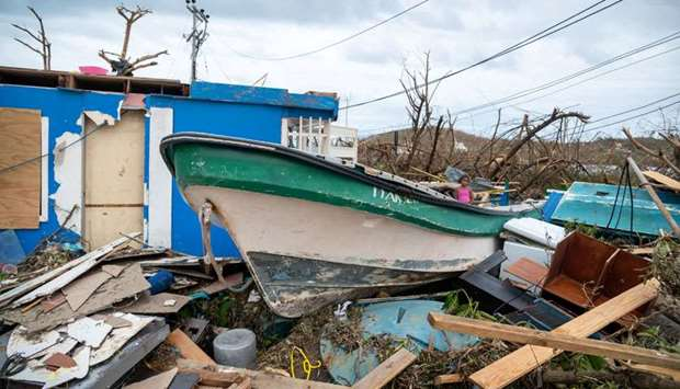 A child stands in a fishing boat amid debris after the passing of Storm Iota, in Santa Catalina