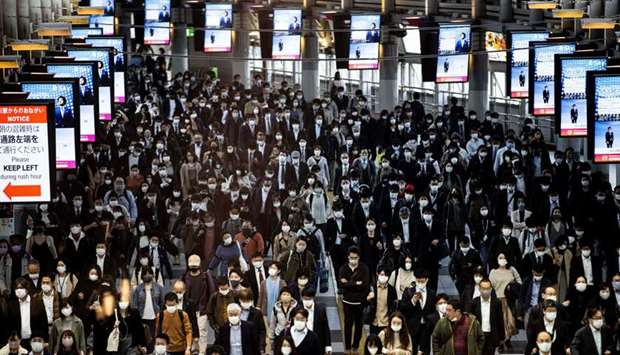 Commuters wearing face masks walk at Shinagawa Station in Tokyo