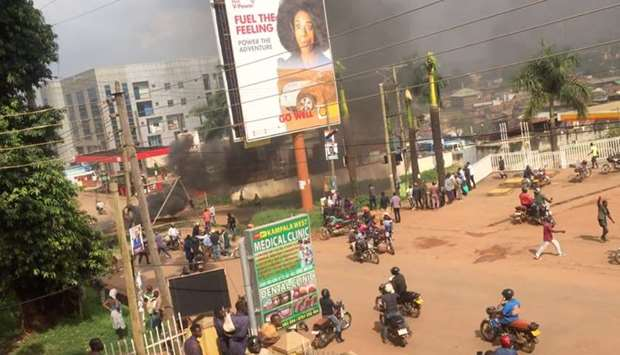 People ride motorcycles as smoke rises from burning objects in a street in Kampala, Uganda November