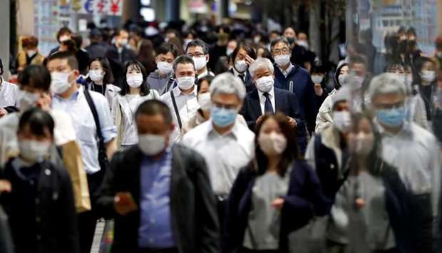 People wearing protective face masks walk on the street, amid the coronavirus disease outbreak, in T