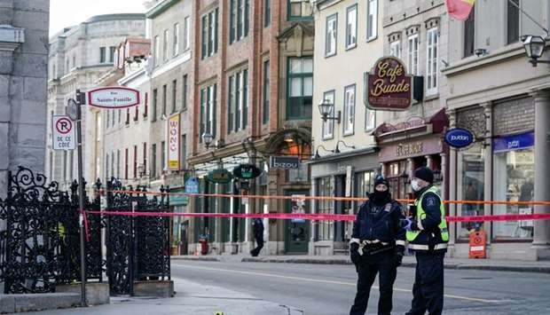 Police officers secure the area where multiple people were stabbed near the Parliament Hill area of