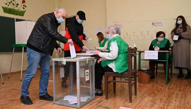 A man casts his ballot at a polling station as part of Georgia's parliamentary runoff elections in T