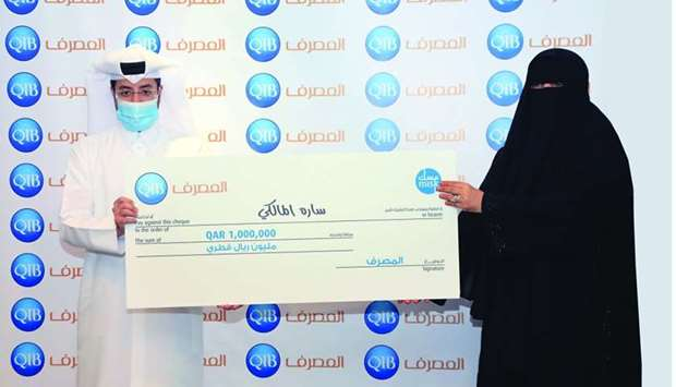 QIB customer Sara al-Malki receiving the grand prize at QIB's head office