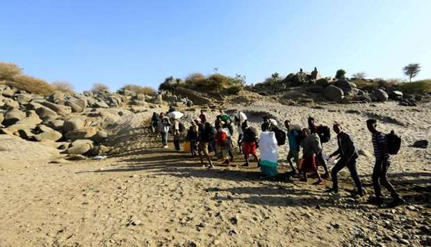 Ethiopians who fled the ongoing fighting in Tigray region, carry their belongings from a boat after