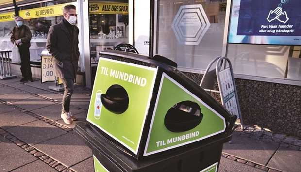 Pedestrian passes a waste bin for disposable masks in Aarhus, Denmark. Aarhus municipality have plac