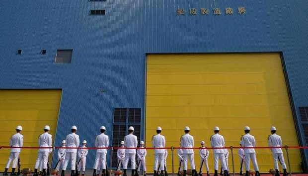 Taiwanese Navy honour guards stand in front of a CSBC shipyard during a ceremony about the construct