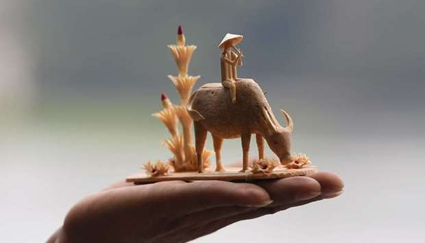 A craftman shows a bamboo miniature sculpture