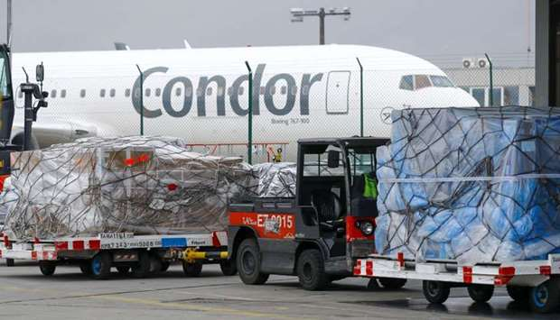 Sealed pallets of air cargo stand near a Condor aircraft at the airfreight depot, operated by Frankf