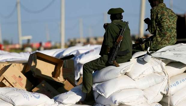 Armed men guard sacks of food delivered to Ethiopian refugees fleeing from the ongoing fighting in T