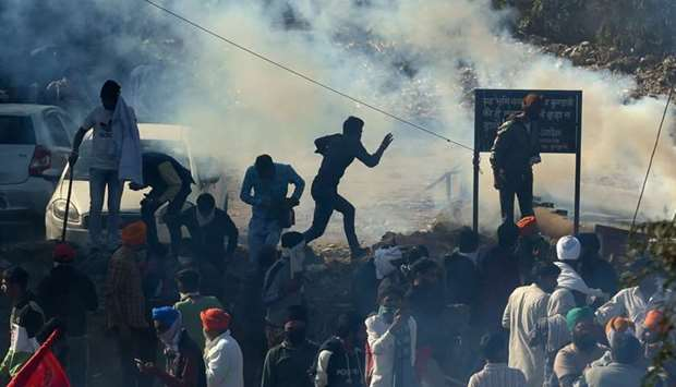 Police fire tear gas to disperse farmers at a roadblock as they try to march to New Delhi to protest